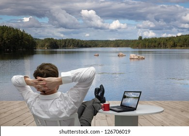 Businessman resting on the shore of lake