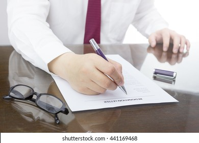 Businessman review his resignation letter on his desk before sending to his boss to quit his job with eye glasses.