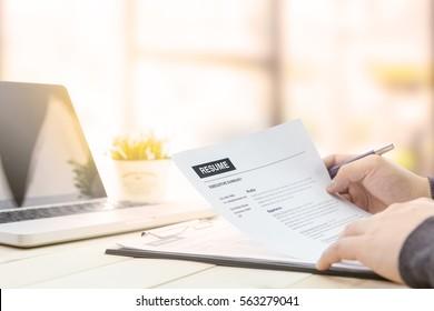 Der Geschäftsmann überprüft seinen Lebenslauf auf seinem Holzschreibtisch, bevor er einen Job mit Laptop-Computer, Uhr und Brille zu finden schickt.