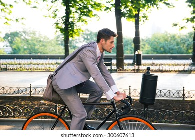 Businessman riding bicycle to work in city park