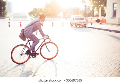 Businessman riding bicycle to work in town