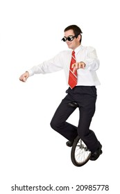 Businessman riding on mono-cycle - concept for reckless business and risk taking - isolated
