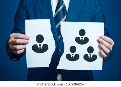 Businessman ripped a piece of paper as a symbol of disagreement in the team. Dismissing one team member. Businessman removes / dismisses the employee from the team