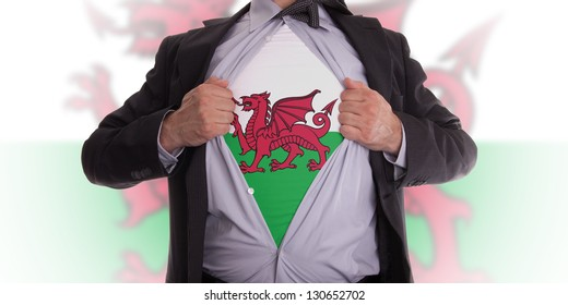 Businessman rips open his shirt to show his Welsh flag t-shirt