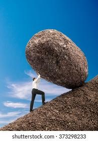 Businessman rolling up giant boulder on slope over blue sky