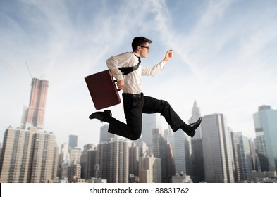 Businessman running fast with cityscape in the background