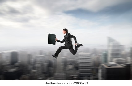 Businessman running fast over a city