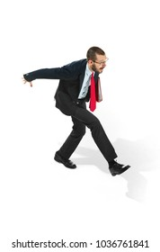 Businessman running with a folder isolated on white background. Serious bearded young man in glasses, suit late and running. Business, career, success, late concept.