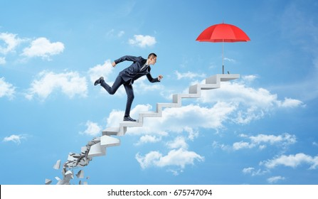 A businessman running up on crumbling concrete steps through the clouds to reach a red umbrella. Business protection. Hostile market environment. Survival strategy.