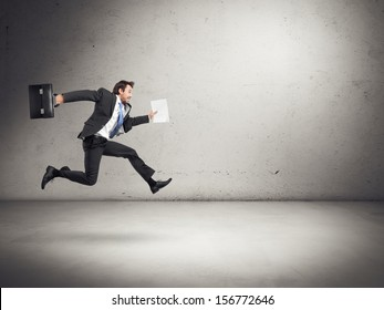 businessman running with papers and briefcase in his hands
