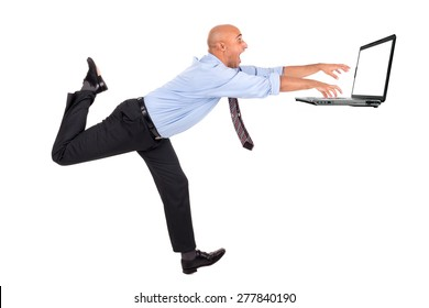 Businessman running with raised arms chasing a laptop, isolated in white