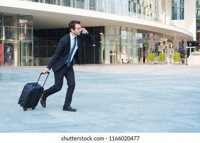 Businessman running with rolling bag and talking on the phone