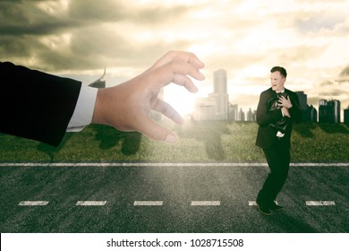 Businessman running scare being chased by a debt collector huge hand