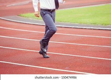 A businessman is running in the sports track