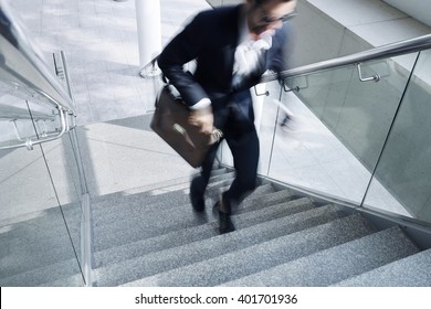 Businessman running up the stair, blurred motion