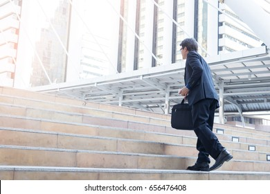 Businessman running or walking on stairs, modern city background, Businessmen Success concept.