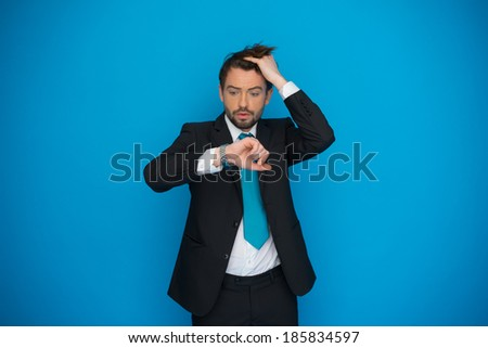 businessman in rush looking at his watch , running late on blue