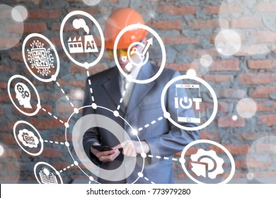 Businessman in safety helmet using virtual iinovative industrial interface with smartphone. Modern Smart Manufacturing.