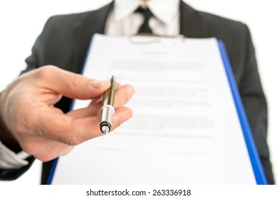 Businessman or salesman handing over a contract attached to a clipboard for signature offering a ballpoint pen in his hand with focus to the pen.