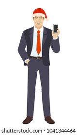 Businessman in Santa hat with hand in pocket and with mobile phone. Full length portrait of businessman in a flat style. Raster illustration.