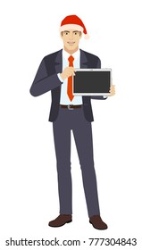 Businessman in Santa hat showing blank digital tablet PC. Full length portrait of businessman in a flat style. Raster illustration.
