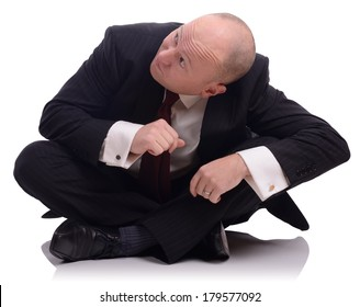 Businessman sat on the floor looking up and ducking down, isolated on a white background