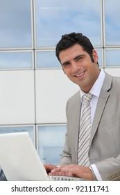 Businessman sat outside modern office block