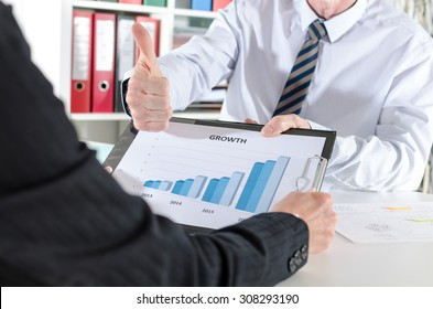 Businessman satisfied with the results showing his thumb up