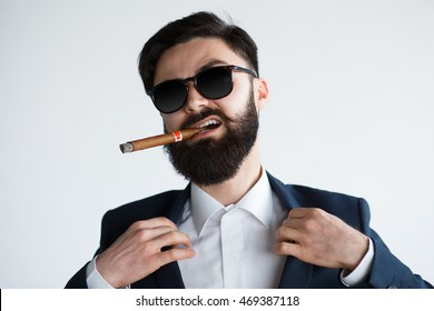Businessman savoring success with a cigar - isolated on white background. Succesful black suit bearded man close up portrait