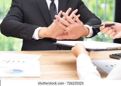 Businessman says no or hold on when businesswoman giving pen for signing a contract.