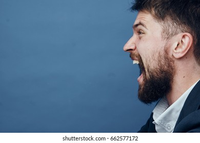 Businessman screaming, businessman with a beard, businessman on a blue background.