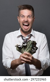 Businessman screaming with burning dollars on dark grey. Short-haired man in white shirt annoyed by bankrupcy of his company.