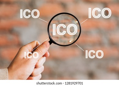Businessman search ICO Initial Coin Offering virtual digital electronic user interface magnifier.