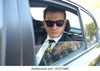 Businessman seated in  a luxury car