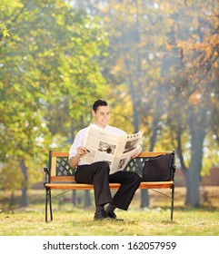 Businessman seated on a wooden bench reading a newspaper in a park, shot with a tilt and shift lens