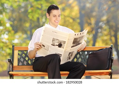 Businessman seated on a wooden bench reading a newspaper in a park