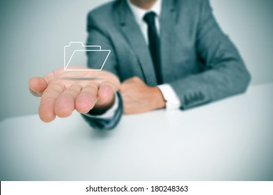 a businessman seating in a desk holding a folder icon in his hand