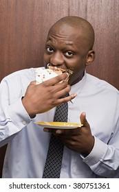 Businessman secretly eating cake
