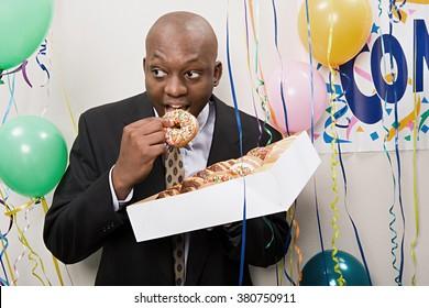 Businessman secretly eating doughnuts