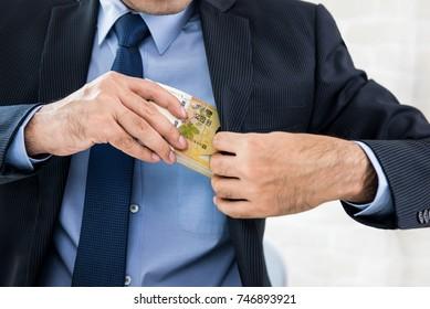 Businessman secretly keeping money, Korean won banknotes, in his suit pocket