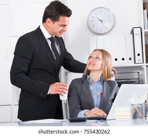 Businessman seducing female colleague while working on laptop in office