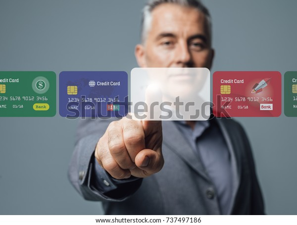 Businessman selecting a credit card on a visual interactive interface and choosing a payment method, he is touching a blank card; online banking and payments concept