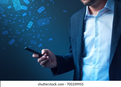 Businessman sending bulk messages using smartphone, male business person in elegant suit delivering e-mails, newsletters or SMS text messages with his mobile phone app