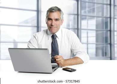 businessman senior gray hair working laptop interior modern white office [Photo Illustration]