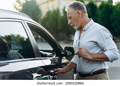 Businessman senior man gets into his car after a hard work day