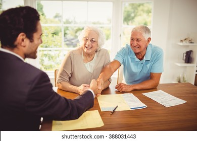 Businessman and senior man handshaking at home