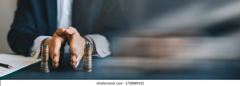 Businessman separates stack coins. Property division. Divorce and legal services. Concept of  saving and investing. Panoramic bussiness banner with copy space.