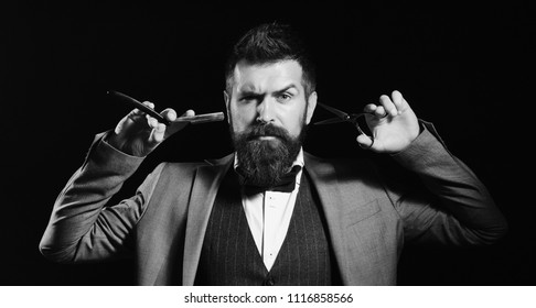 Businessman with serious face isolated on black background. Macho in formal suit cuts and shaves beard. Man with long beard holds shaving razor and scissors. Business and barbershop service concept.