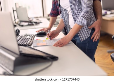 Businessman sexualy harassing female colleague during working hours at a workplace. Focus on the woman's hand holding a pen