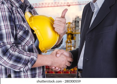 businessman shake hands with engineering construction site